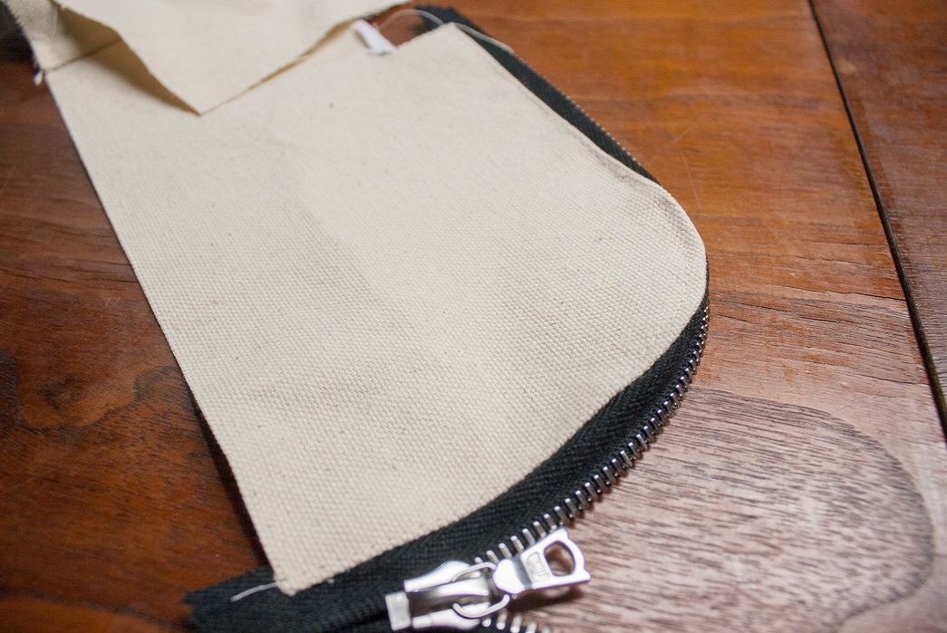 Running a stitch around the zipper on the body of the wallet