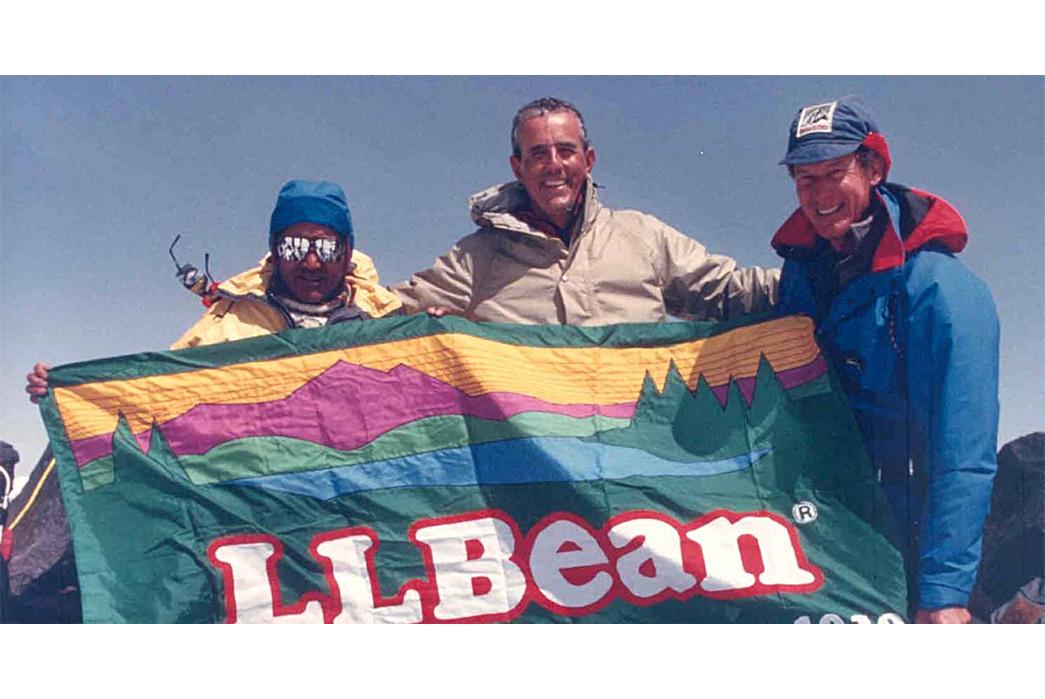 L.L.-Bean-History,-Philosophy,-and-Iconic-Products-Leon-Gorman-(centre)-holding-an-L.L.-Bean-flag-featuring-the-Sunrise-over-Katadhin-logo-via-L.L.-Bean